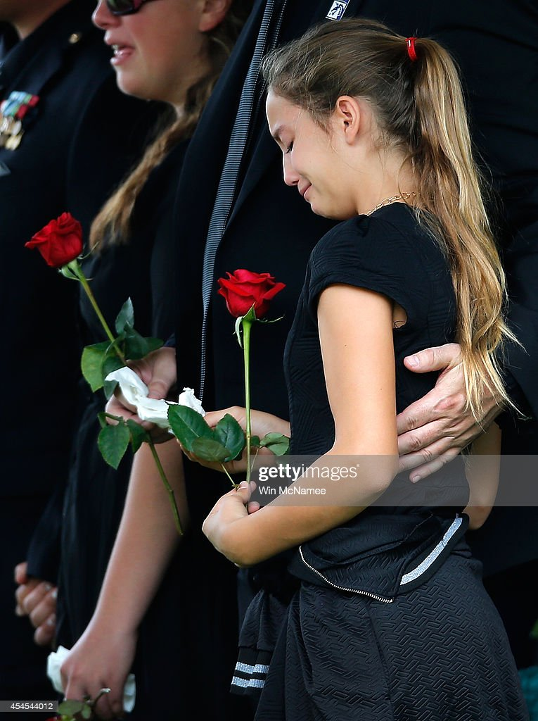 Kendra Leggett (R), the neice of Sgt. First Class Matthew Leggett, attends the burial service for her uncle at Arlington National Cemetery September 3, 2014 in Arlington, Virginia. Leggett, a paratrooper stationed at Ft. Bragg who received the Bronze Star Medal and Purple Heart, was killed in action on August 20, 2014 while serving his third tour of Afghanistan.
