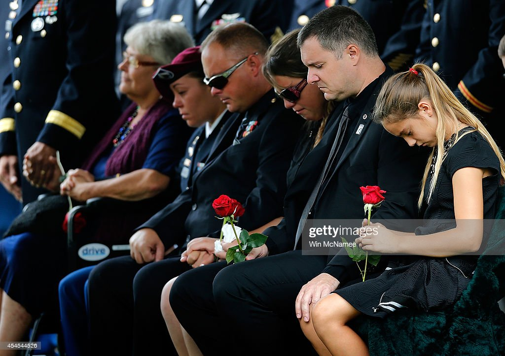 Kendra Leggett (R), the neice of Sgt. First Class Matthew Leggett, joins family members in attending the burial service for her uncle at Arlington National Cemetery September 3, 2014 in Arlington, Virginia. Leggett, a paratrooper stationed at Ft. Bragg who received the Bronze Star Medal and Purple Heart, was killed in action on August 20, 2014 while serving his third tour of Afghanistan. Also pictured (L) is Leggett's mother, Thea Kurz.