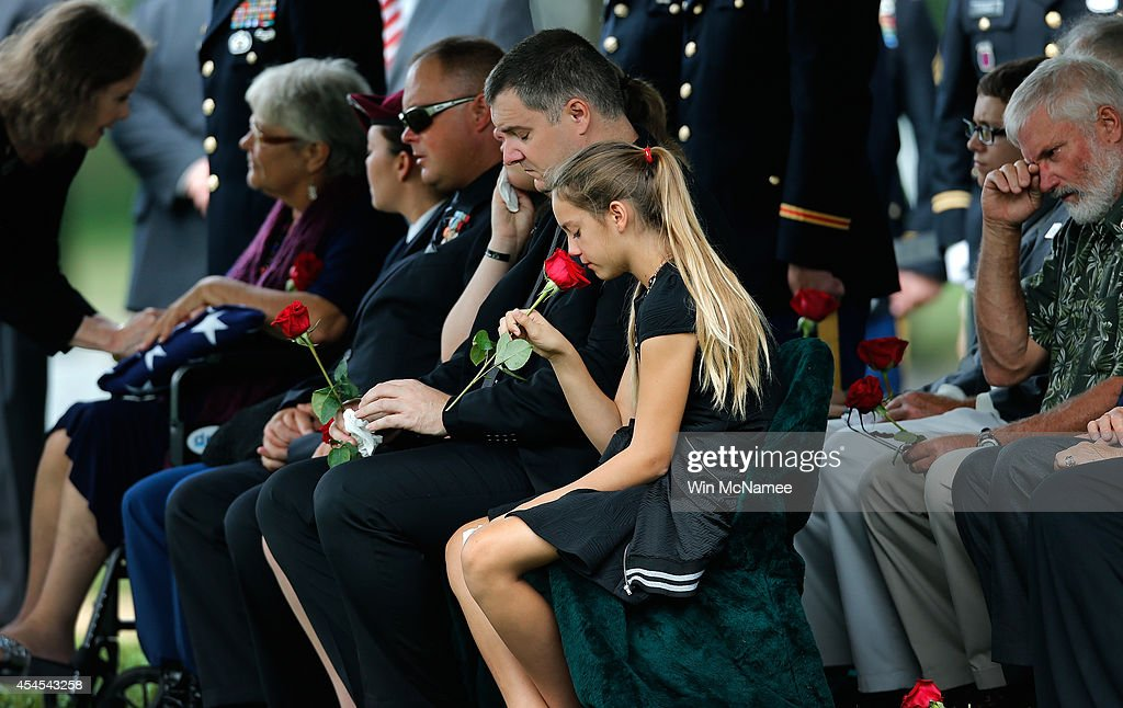 Kendra Leggett, the neice of Sgt. First Class Matthew Leggett, smells a red rose while attending the burial service for her uncle at Arlington National Cemetery September 3, 2014 in Arlington, Virginia. Leggett, a paratrooper stationed at Ft. Bragg who received the Bronze Star Medal and Purple Heart, was killed in action on August 20, 2014 while serving his third tour of Afghanistan. Also pictured (L) is Leggett's mother, Thea Kurz.