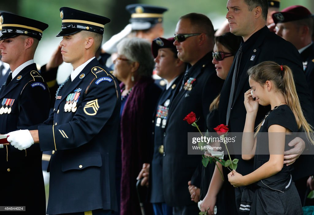 Kendra Leggett (R), the neice of Sgt. First Class Matthew Leggett, wipes tears from her eyes while attending the burial service for her uncle at Arlington National Cemetery September 3, 2014 in Arlington, Virginia. Leggett, a paratrooper stationed at Ft. Bragg who received the Bronze Star Medal and Purple Heart, was killed in action on August 20, 2014 while serving his third tour of Afghanistan.