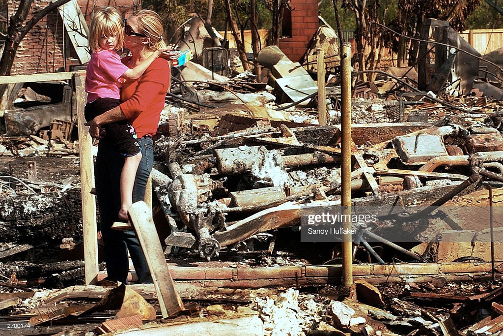 Kendra Lipka hugs her daughter Rachel, 5, after seeing their home in ruins October 29, 2003 in the Scripps Ranch area of San Diego, California. Residents were allowed to back to their homes after the Crest wildfire erupted on October 26, destroying over 100 homes in the area.