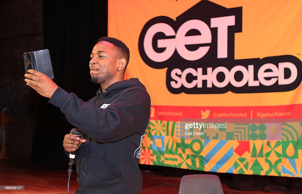 Kendrick Lamar takes a video of the crowd from the stage with his smartphone while visiting Providence, Rhode Island students with the Get Schooled victory tour at the Mt. Pleasant High School on May 10, 2013 in Providence, Rhode Island.