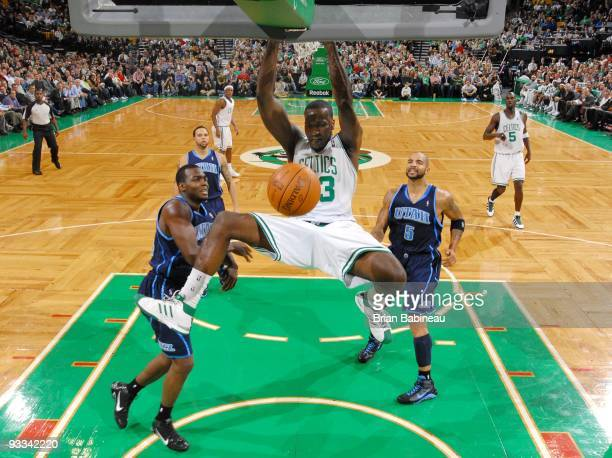 Kendrick Perkins of the Boston Celtics dunks against Paul Millsap and Carlos Boozer of the Utah Jazz during the game at The TD Garden on November 11...