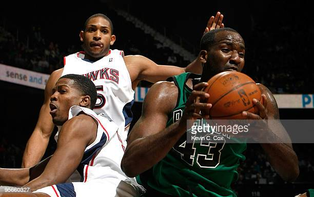 Kendrick Perkins of the Boston Celtics grabs a rebound against Joe Johnson and Al Horford of the Atlanta Hawks at Philips Arena on January 8 2010 in...
