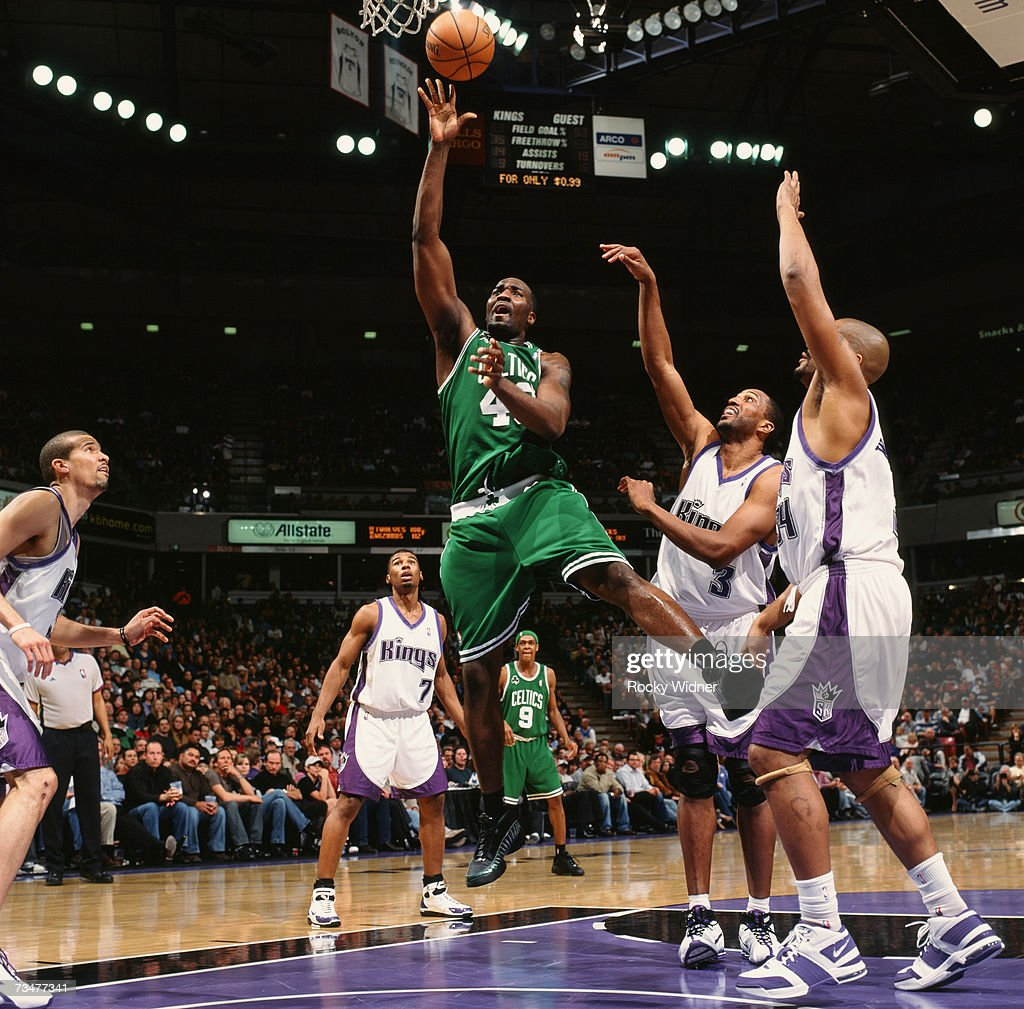 Kendrick Perkins of the Boston Celtics shoots a layup against Shareef AbdurRahim and Corliss Williamson of the Sacramento Kings during a game at Arco...