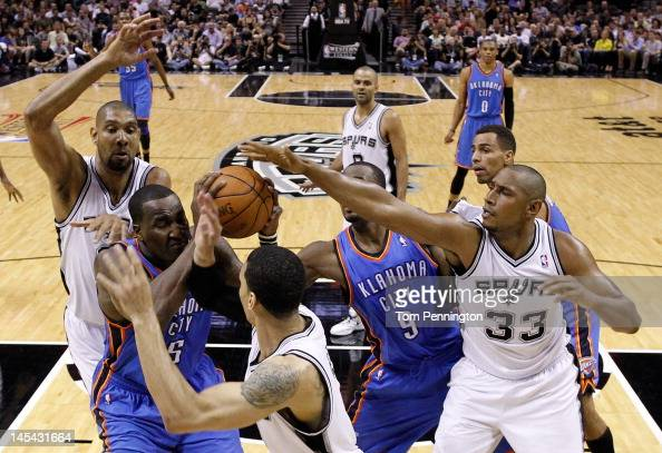 Kendrick Perkins of the Oklahoma City Thunder holds the ball as Tim Duncan Daniel Green and Boris Diaw of the San Antonio Spurs attempt to block his...
