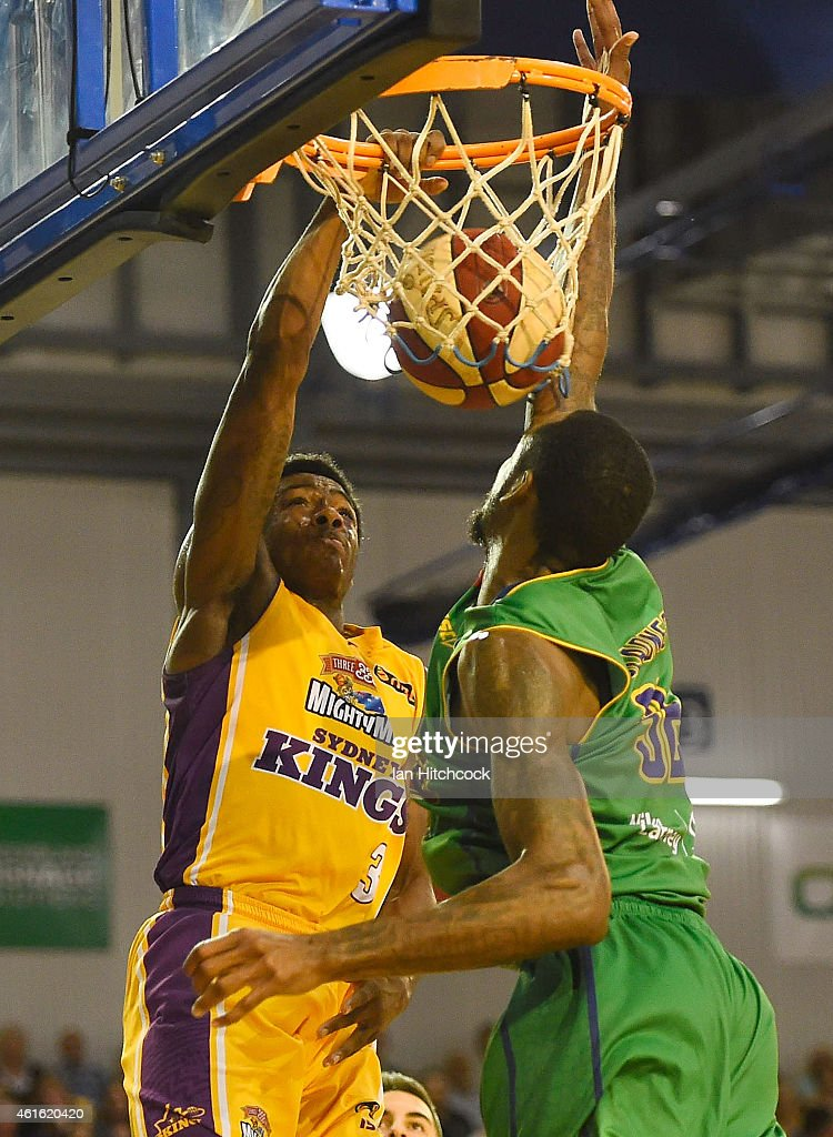 Kendrick Perry of the Kings slam dunks the ball in front of Mickell Gladness of the Crocodiles during the round 15 NBL match between the Townsville Crocodiles and Sydney Kings at Townsville RSL Stadium on January 16, 2015 in Townsville, Australia.