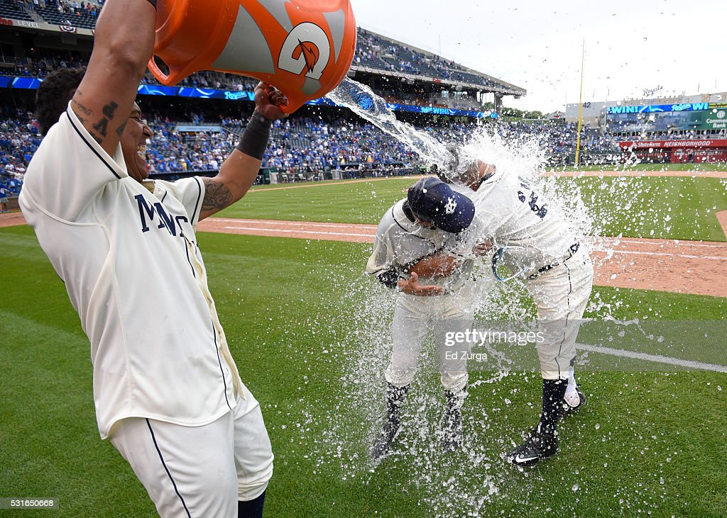 Kendrys Morales #25 of the Kansas City Royals and catching coach Pedro Grifol #28 are doused with water by Salvador Perez #13 as they celebrate a 4-2 win against the Atlanta Braves in 13 innings at Kauffman Stadium on May 15, 2016 in Kansas City, Missouri.