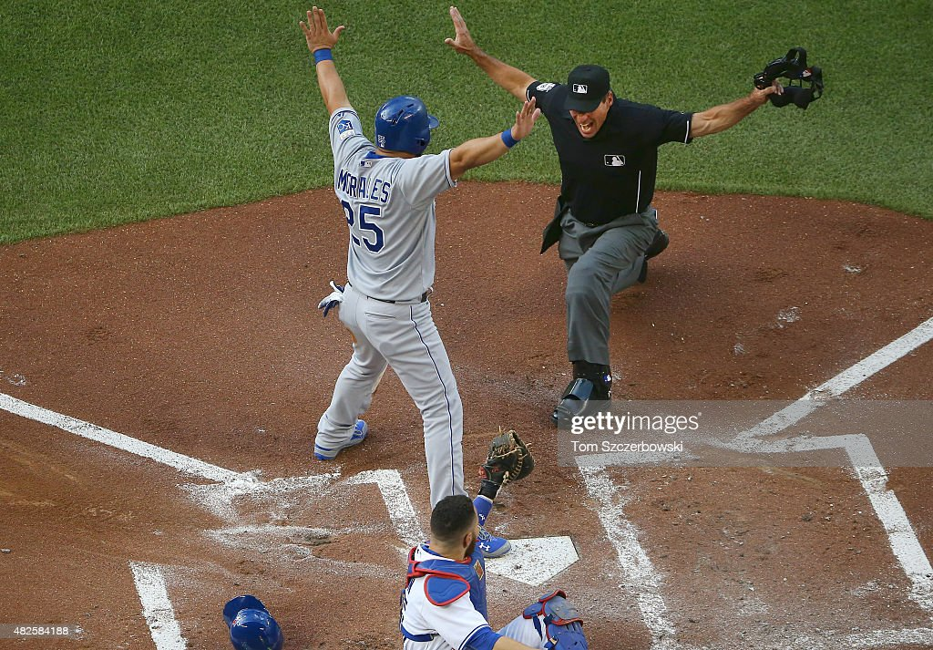Kendrys Morales #25 of the Kansas City Royals is called safe at home plate to score a run in the first inning during MLB game action as <a gi-track='captionPersonalityLinkClicked' href=/galleries/search?phrase=Russell+Martin+-+Baseball+Player&family=editorial&specificpeople=13764024 ng-click='$event.stopPropagation()'>Russell Martin</a> #55 of the Toronto Blue Jays shows the ball to home plate umpire <a gi-track='captionPersonalityLinkClicked' href=/galleries/search?phrase=Angel+Hernandez&family=editorial&specificpeople=242828 ng-click='$event.stopPropagation()'>Angel Hernandez</a> #55 on July 31, 2015 at Rogers Centre in Toronto, Ontario, Canada.