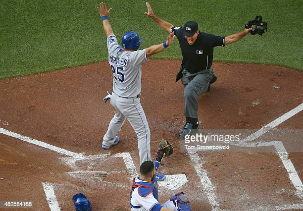 Kendrys Morales of the Kansas City Royals is called safe at home plate to score a run in the first inning during MLB game action as Russell Martin of...