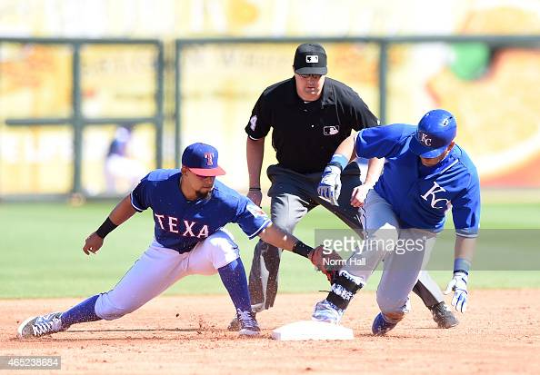 Kendrys Morales of the Kansas City Royals slides safely into second base just ahead of the tag of Rougned Odor of the Texas Rangers on March 4 2015...