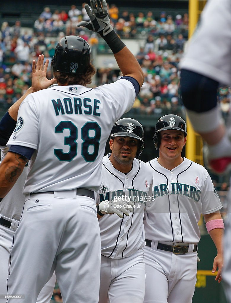 Kendrys Morales #8 (C) of the Seattle Mariners is congratulated by Michael Morse #38 after hitting a three-run home run in the first inning against the Oakland Athletics at Safeco Field on May 12, 2013 in Seattle, Washington. Kyle Seager #15 is at right.