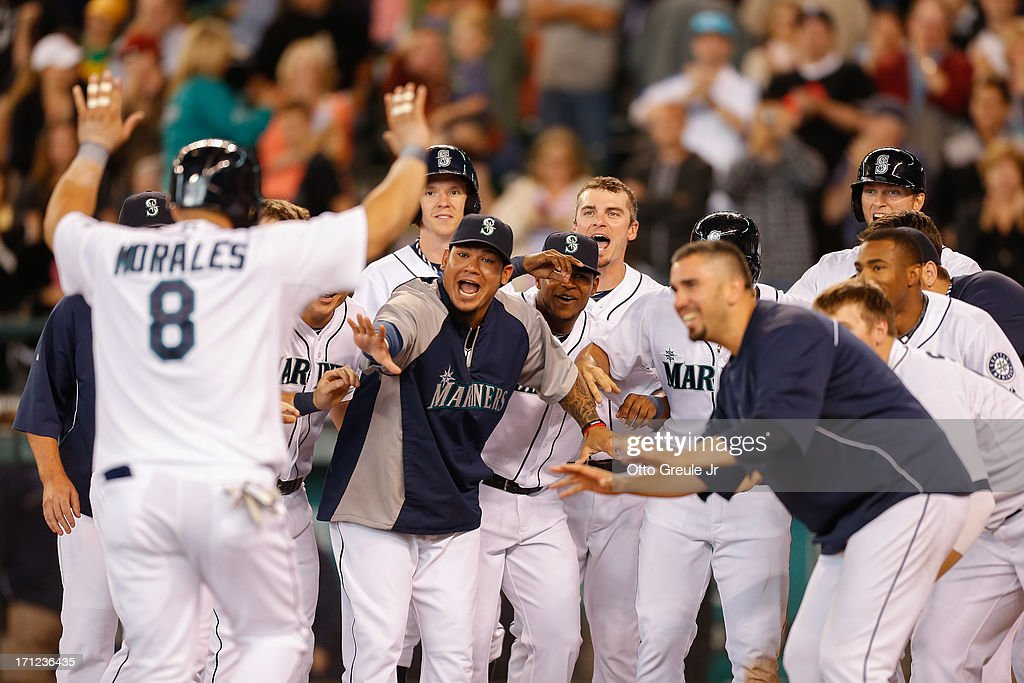 Kendrys Morales #8 of the Seattle Mariners is congratulated by teammates after hitting a walk-off three-run home run in the tenth inning against the Oakland Athletics at Safeco Field on June 23, 2013 in Seattle, Washington. The Mariners defeated the Athletics 6-3.