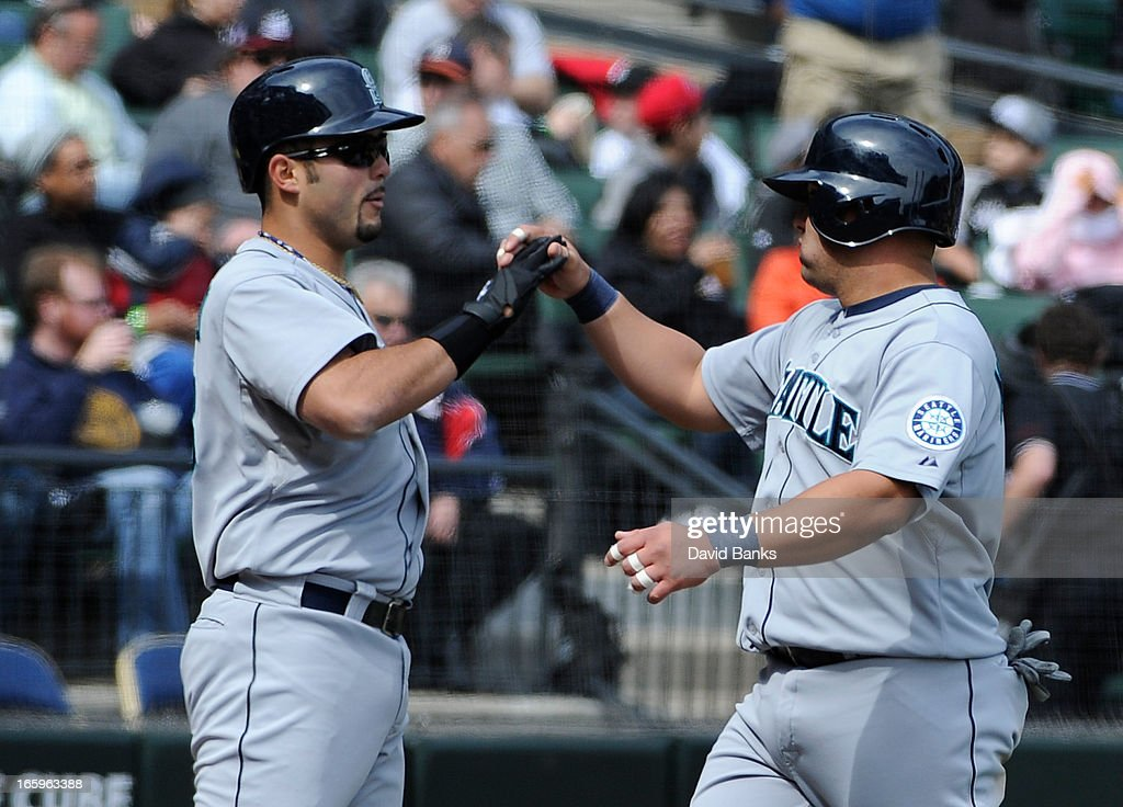 Kendrys Morales (R) of the Seattle Mariners is greeted by <a gi-track='captionPersonalityLinkClicked' href=/galleries/search?phrase=Jesus+Montero&family=editorial&specificpeople=4900196 ng-click='$event.stopPropagation()'>Jesus Montero</a> #63 after hitting a home-run against the Chicago White Sox in the sixth inning on April 7, 2013 at U.S. Cellular Field in Chicago, Illinois.
