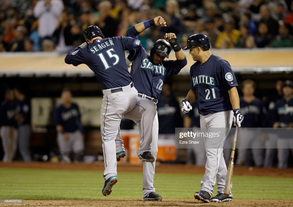 Kendrys Morales #21 of the Seattle Mariners looks on as <a gi-track='captionPersonalityLinkClicked' href=/galleries/search?phrase=Robinson+Cano&family=editorial&specificpeople=538362 ng-click='$event.stopPropagation()'>Robinson Cano</a> #22 and <a gi-track='captionPersonalityLinkClicked' href=/galleries/search?phrase=Kyle+Seager&family=editorial&specificpeople=7682389 ng-click='$event.stopPropagation()'>Kyle Seager</a> #15 celebrate after Seager hit a two-run home run that scored Cano in the fifth inning of their game against the Oakland Athletics at O.co Coliseum on September 2, 2014 in Oakland, California.