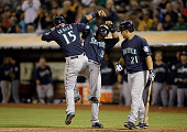 Kendrys Morales of the Seattle Mariners looks on as Robinson Cano and Kyle Seager celebrate after Seager hit a tworun home run that scored Cano in...
