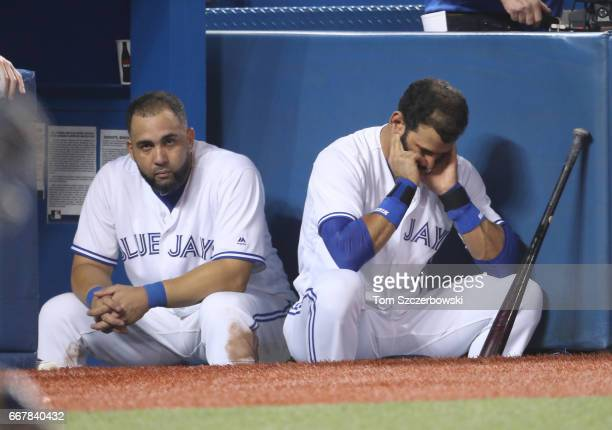 Kendrys Morales of the Toronto Blue Jays and Jose Bautista look on from the top step of the dugout during MLB game action against the Milwaukee...