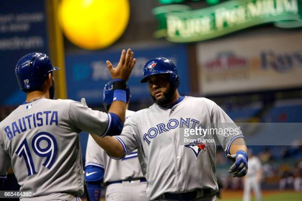 Kendrys Morales of the Toronto Blue Jays celebrates at home plate with teammate Jose Bautista after hitting a grand slam off of pitcher Blake Snell...