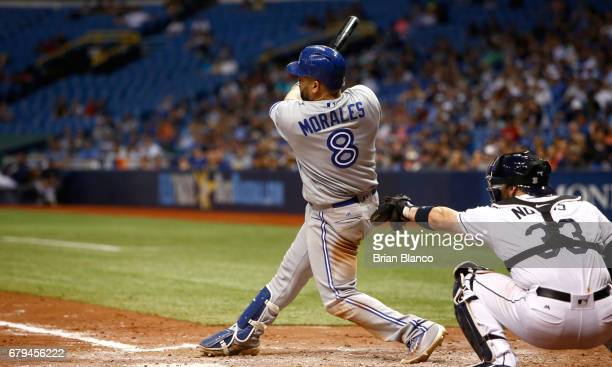 Kendrys Morales of the Toronto Blue Jays follows through on his swing as he hits a threerun home run in front of catcher Derek Norris of the Tampa...