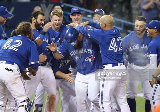 Kendrys Morales of the Toronto Blue Jays is congratulated at home plate by teammates after hitting a gamewinning solo home run in the ninth inning...