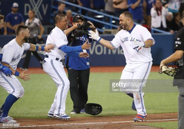 Kendrys Morales of the Toronto Blue Jays is congratulated by Ezequiel Carrera after hitting a gamewinning solo home run in the ninth inning during...