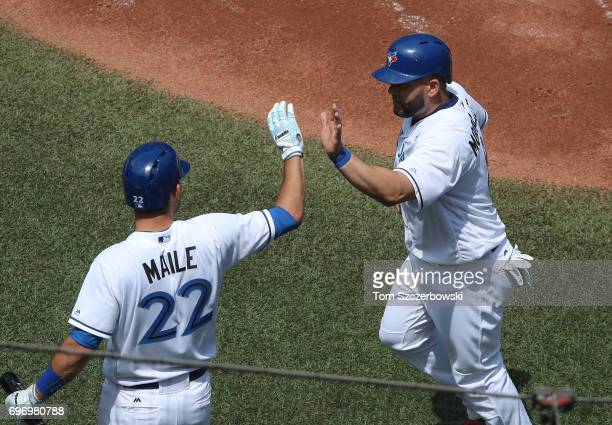 Kendrys Morales of the Toronto Blue Jays is congratulated by Luke Maile after scoring a run in the second inning during MLB game action against the...