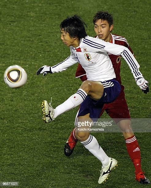 Kengo Nakamura of Japan controls the ball with Chin Hung Wong of Hong Kong during the East Asian Football Championship 2010 match between Japan and...