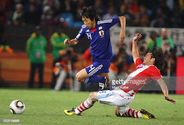 Kengo Nakamura of Japan is tackled by Nelson Valdez of Paraguay during the 2010 FIFA World Cup South Africa Round of Sixteen match between Paraguay...