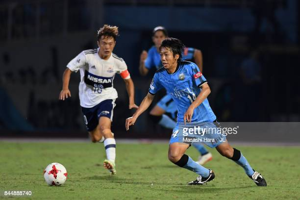 Kengo Nakamura of Kawasaki Frontale controls the ball under pressure of Manabu Saito of Yokohama FMarinos during the JLeague J1 match between...