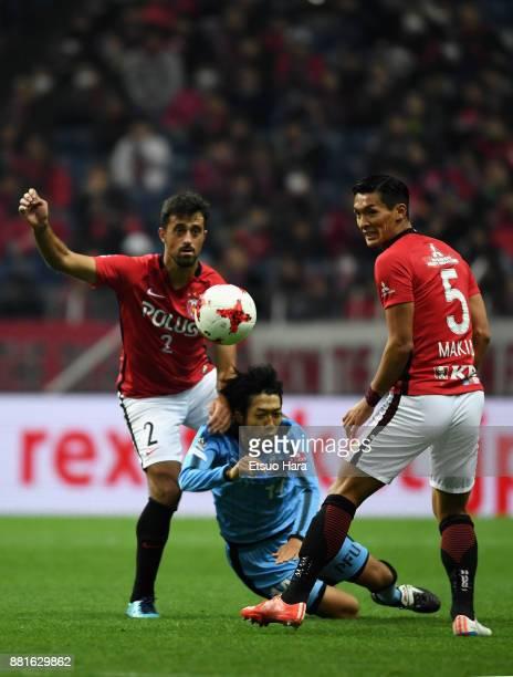 Kengo Nakamura of Kawasaki Frontale is challenged by Tomoaki Makino and Mauricio of Urawa Red Diamonds during the JLeague J1 match between Urawa Red...