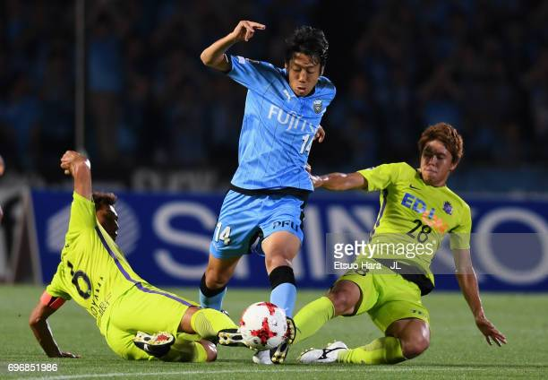 Kengo Nakamura of Kawasaki Frontale is tackled by Toshihiro Aoyama and Takuya Marutani of Sanfrecce Hiroshima during the JLeague J1 match between...