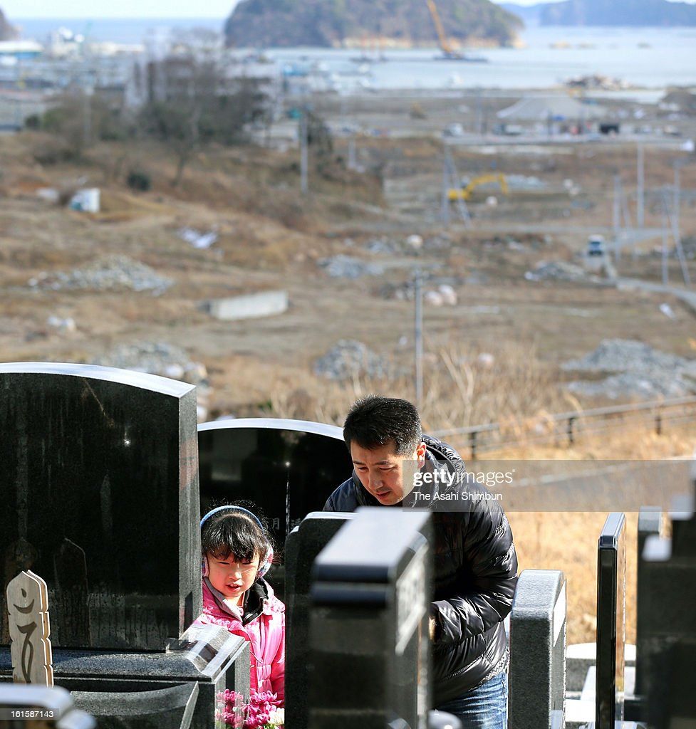 Kengo Sasaki (R) visit the grave of his wife Naoko who was killed by the tsunami triggered by the Great East Japan Earthquake, with his daughter Chihiro, on February 11, 2013 in Minamisanriku, Miyagi, Japan. 2 year anniversary approaches though the restoration from the earthquake and tsunami have been delayed.