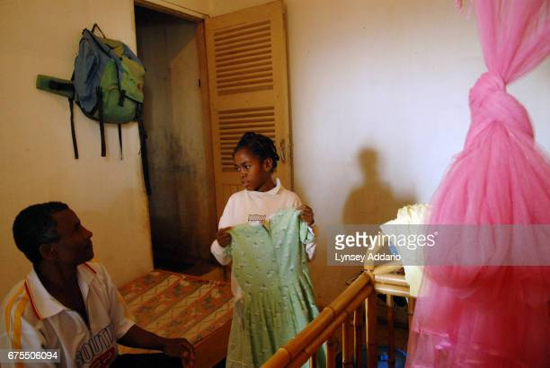 Kenia Moravelo holds up a new dress to her father Antoine Moravelo at the shelter where she has been staying since released from her most recent stay...