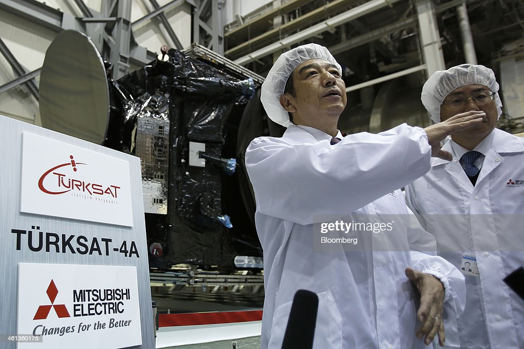 Kenichiro Yamanishi, president and chief executive officer of Mitsubishi Electric Corp., left, speaks to members of the media following a ceremony marking the shipment of Turksat AS's Turksat-4A communications satellite, manufactured by Mitsubishi Electric Corp., at the company's satellite production facility at Kamakura Works in Kamakura, Kanagawa Prefecture, Japan, on Wednesday, Jan. 8, 2014. Turksat AS is Turkey's state-owned satellite operator. Photographer: Kiyoshi Ota/Bloomberg via Getty Images