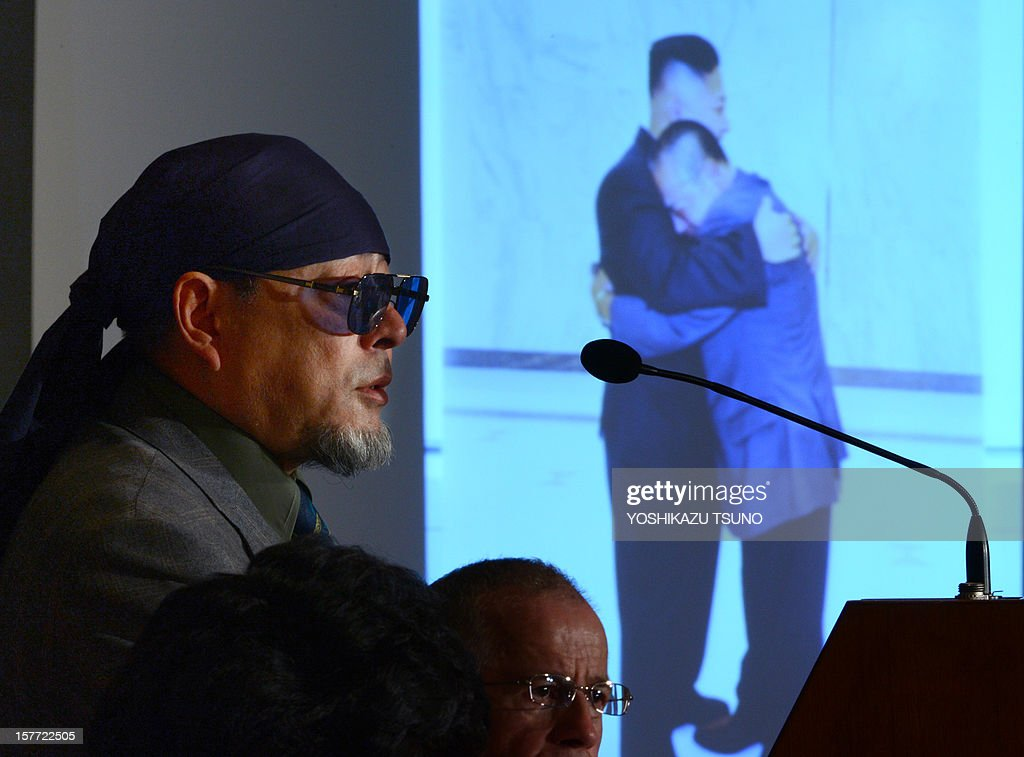 Kenji Fujimoto, former personal chef of late North Korean leader Kim Jong-Il, speaks as a projector displays the cover of his book showing Fujimoto hugging North Korean leader Kim Jong-Un, in Tokyo on December 6, 2012. Fujimoto spoke to foreign journalists about a book he wrote after meeting the country's new leader Kim Jong-Un last July in Pyongyang. AFP PHOTO / Yoshikazu TSUNO