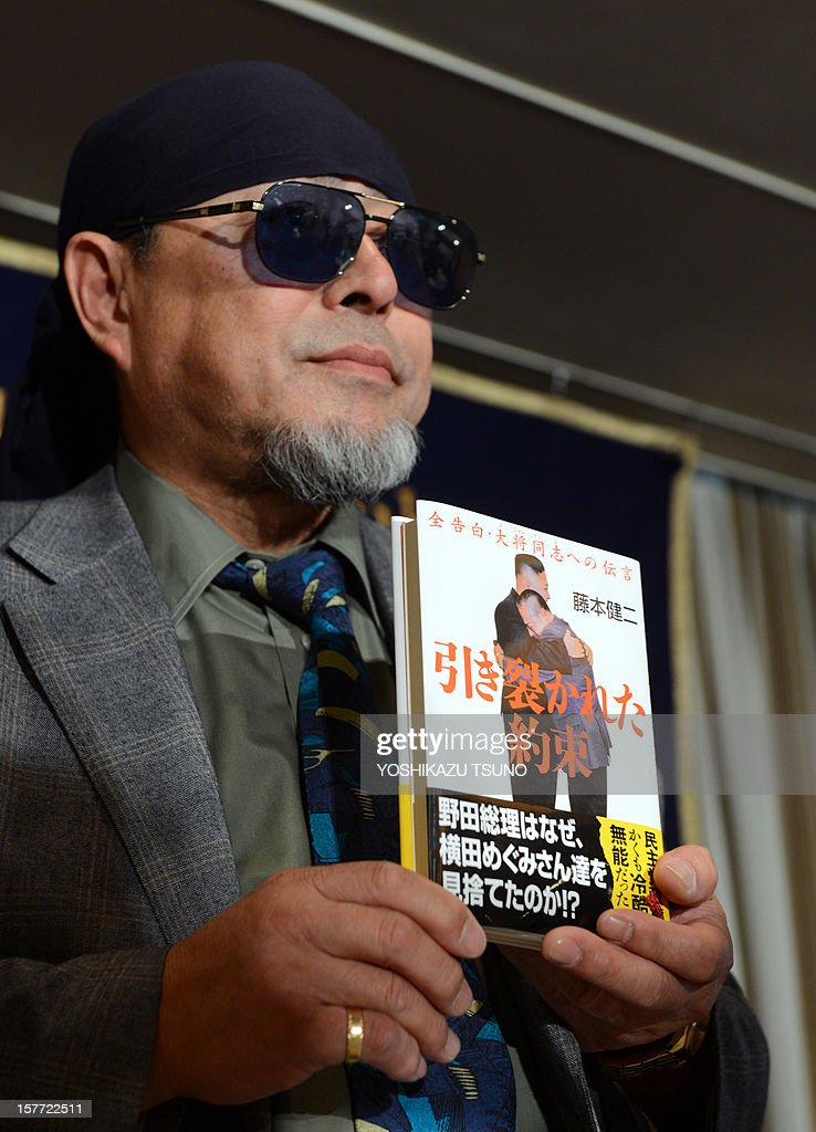 Kenji Fujimoto, former personal chef of late North Korean leader Kim Jong-Il displays his book with a cover picture of Fujimoto hugging North Korean leader Kim Jong-Un, in Tokyo on December 6, 2012. Fujimoto spoke to foreign journalists about a book he wrote after meeting the country's new leader Kim Jong-Un last July in Pyongyang. AFP PHOTO / Yoshikazu TSUNO