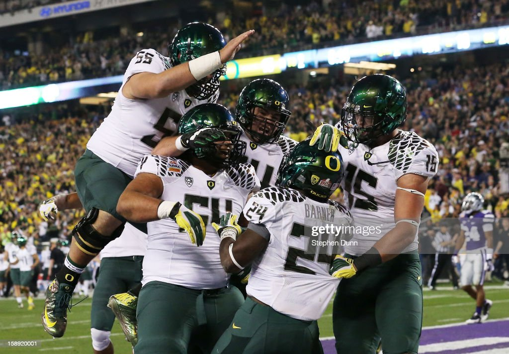 <a gi-track='captionPersonalityLinkClicked' href=/galleries/search?phrase=Kenjon+Barner&family=editorial&specificpeople=6241262 ng-click='$event.stopPropagation()'>Kenjon Barner</a> #24 of the Oregon Ducks celebrates his second quarter touchdown against the Kansas State Wildcats with teammates during the Tostitos Fiesta Bowl at University of Phoenix Stadium on January 3, 2013 in Glendale, Arizona.