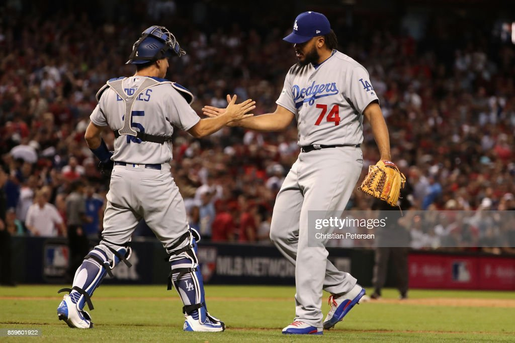 Kenley Jansen #74 of the Los Angeles Dodgers celebrates with Austin Barnes #15 after defeating the Arizona Diamondbacks 3-1 to win the National League Divisional Series at Chase Field on October 9, 2017 in Phoenix, Arizona.