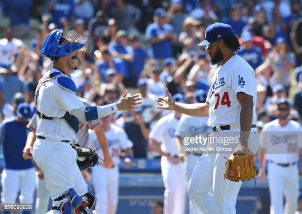 Kenley Jansen of the Los Angeles Dodgers shakes hands with Yasmani Grandal of the Los Angeles Dodgers after the final out of the game against the San...