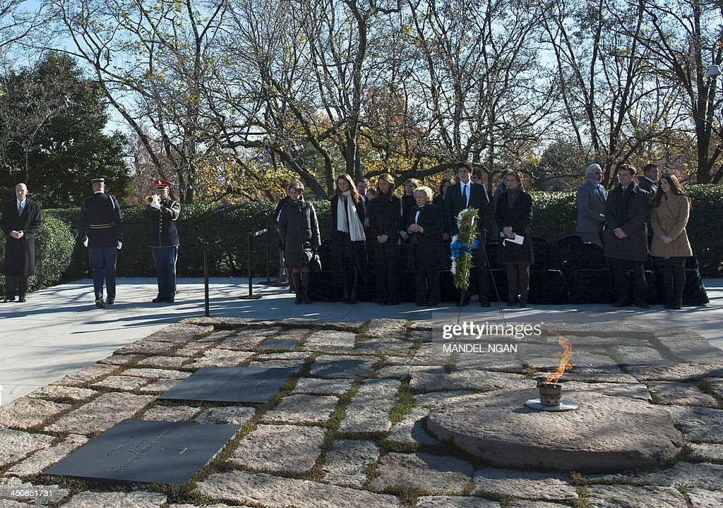 Kennedy family members stand behind the eternal flame at the gravesite of late US President John F. Kennedy before the arrival of US President Barack Obama, First Lady Michelle Obama and former President Bill Clinton and former Secretary of State Hillary Clinton to take part in a wreath-laying ceremony in honor of the late President John F. Kennedy at Arlington National Cemetery on November 20, 2013 in Arlington, Virginia. AFP PHOTO/Mandel NGAN