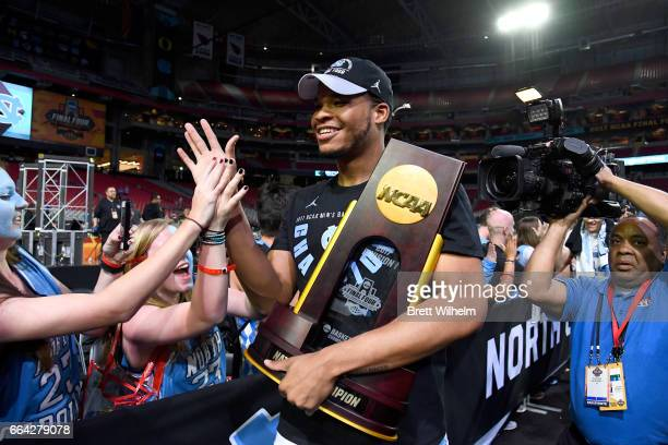 Kennedy Meeks of the North Carolina Tar Heels highfive fans while holding the championship trophy during the 2017 NCAA Men's Final Four National...
