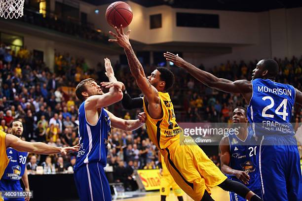 J Kennedy of Ludwigsburg tries to score against Danilo Barthel and Mike Morrison of Frankfurt during the Beko BBL basketball match between MHP Riesen...