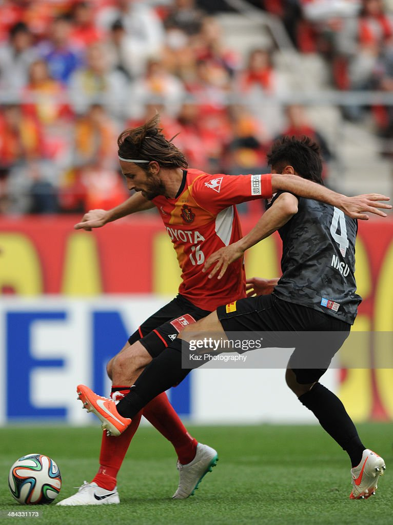 Kennedy (L) of Nagoya Grampus keeps the ball under the pressure from Daisuke Nasu of Urawa Red Diamonds action during the J. League match between Nagoya Grampus and Urawa Red Diamonds at the Toyota Stadium on April 12, 2014 in Toyota, Japan.