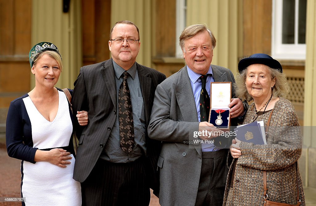 Kenneth Clarke holds his Companion of Honour award with his children Ken Junior and Susan and his wife Gillian after the Investiture ceremony at...