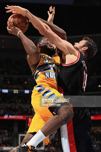 Kenneth Faried of the Denver Nuggets attempts a shot and is fouled by Joel Freeland of the Portland Trail Blazers at Pepsi Center on November 1 2013...