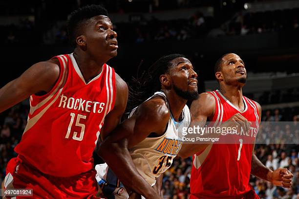 Kenneth Faried of the Denver Nuggets battles for rebounding position against Clint Capela and Trevor Ariza of the Houston Rockets at Pepsi Center on...