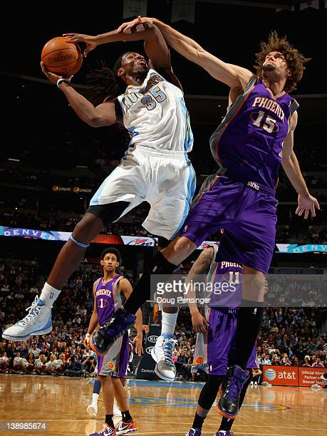 Kenneth Faried of the Denver Nuggets is fouled by Robin Lopez of the Phoenix Suns as he tries to get off a shot at the Pepsi Center on February 14...
