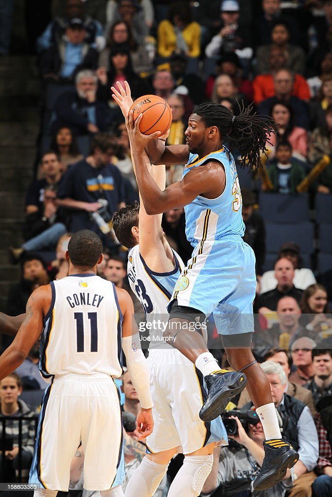 Kenneth Faried #35 of the Denver Nuggets passes against Marc Gasol #33 of the Memphis Grizzlies on December 29, 2012 at FedExForum in Memphis, Tennessee.