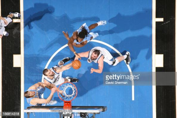 Kenneth Faried of the Denver Nuggets reaches for the ball against Nikola Pekovic and Kevin Love of the Minnesota Timberwolves during the game between...