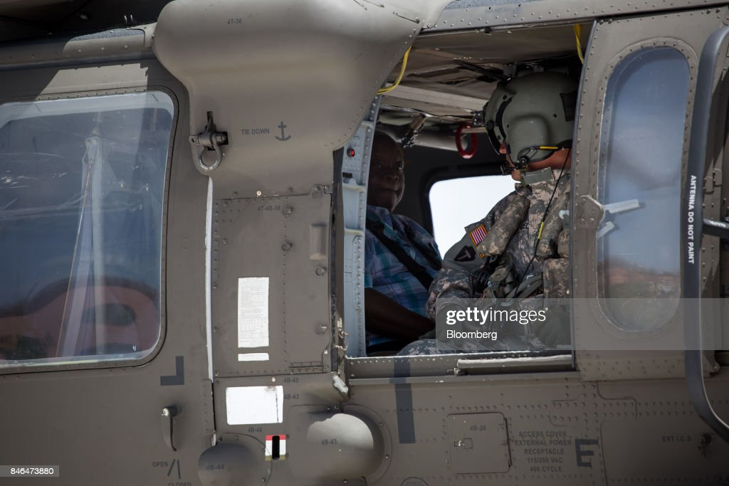 Kenneth Mapp, governor of the U.S. Virgin Islands, left, rides in a military helicopter to access the damage after Hurricane Irma in St John, U.S. Virgin Islands, on Tuesday, Sept. 12, 2017. After being struck by Irma last week, the U.S. Virgin Islands couldn't look less like a tourist destination. Many local residents are giving up and getting out after losing everything to the category 5 storm,even as the local authorities in the U.S. territory say they are determined to rebuild the islands. Photographer: Michael Nagle/Bloomberg via Getty Images